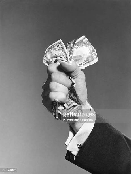 Man's hand clutching wad of dollar bills.