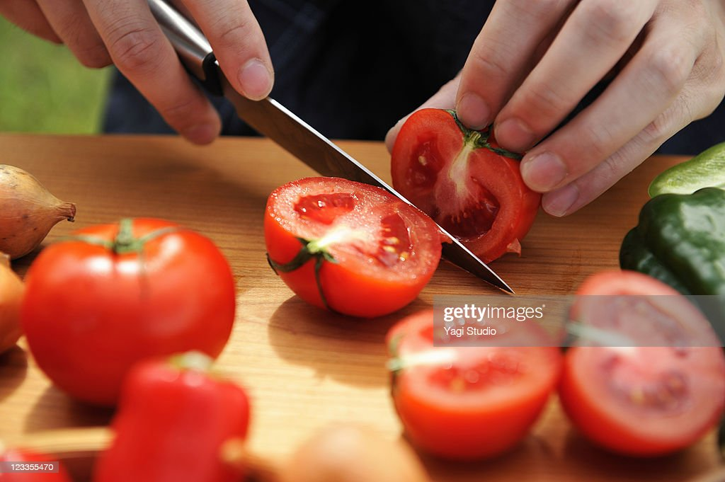 Man's hand cut the tomatoes in outdoor cooking : Stock Photo