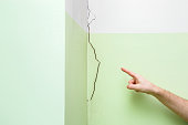 Man's hand finger pointing to cracked corner wall in house. Building problems and solutions concept.
