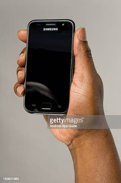 A man's hand holding a Samsung Galaxy S smartphone during a studio shoot for Android App Guide February 11 2011