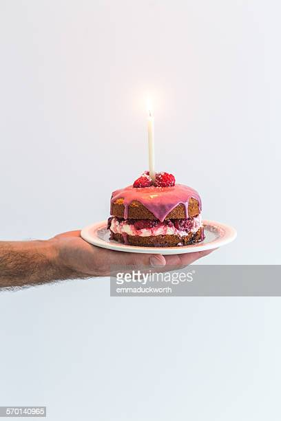 Man's hand holding a victoria sponge birthday cake with a candle
