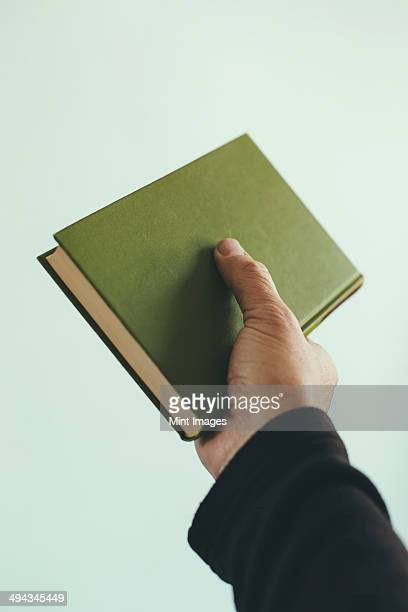 A man's hand holding an old green hardback book.