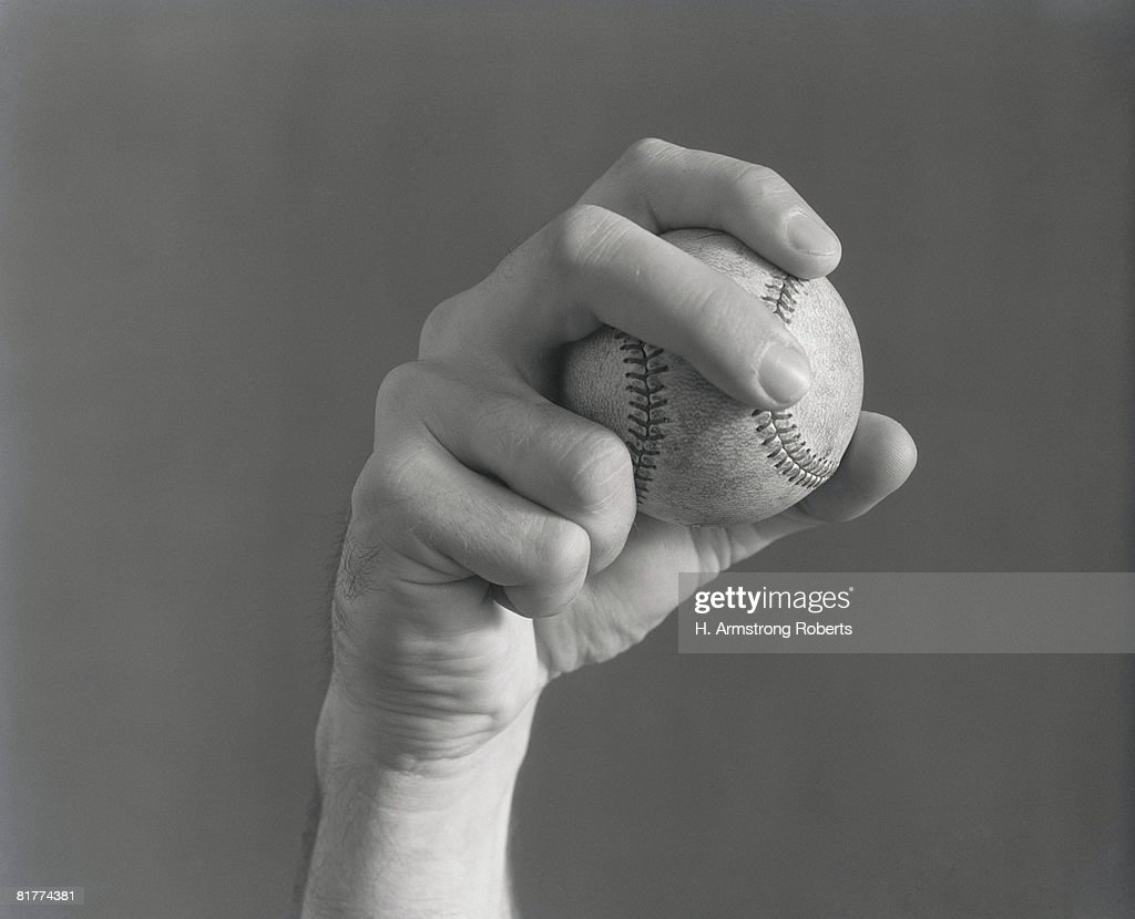 Man's hand holding baseball in pitching form. (Photo by H. Armstrong Roberts/Retrofile/Getty Images) : Stock Photo