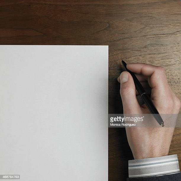 Man's hand holding pen