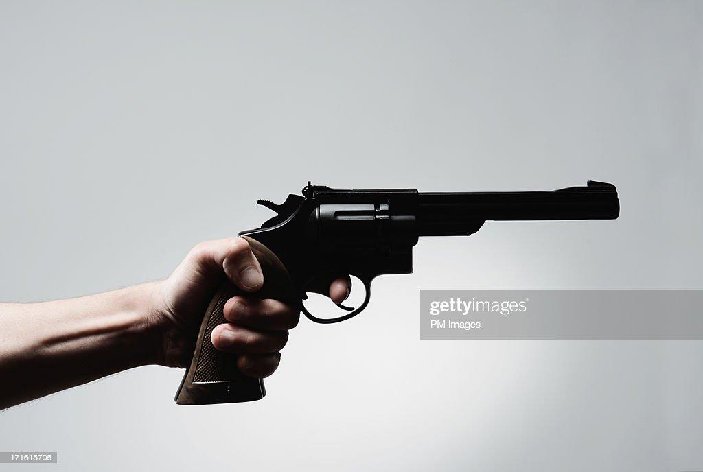 Man's hand holding pistol : Stock Photo