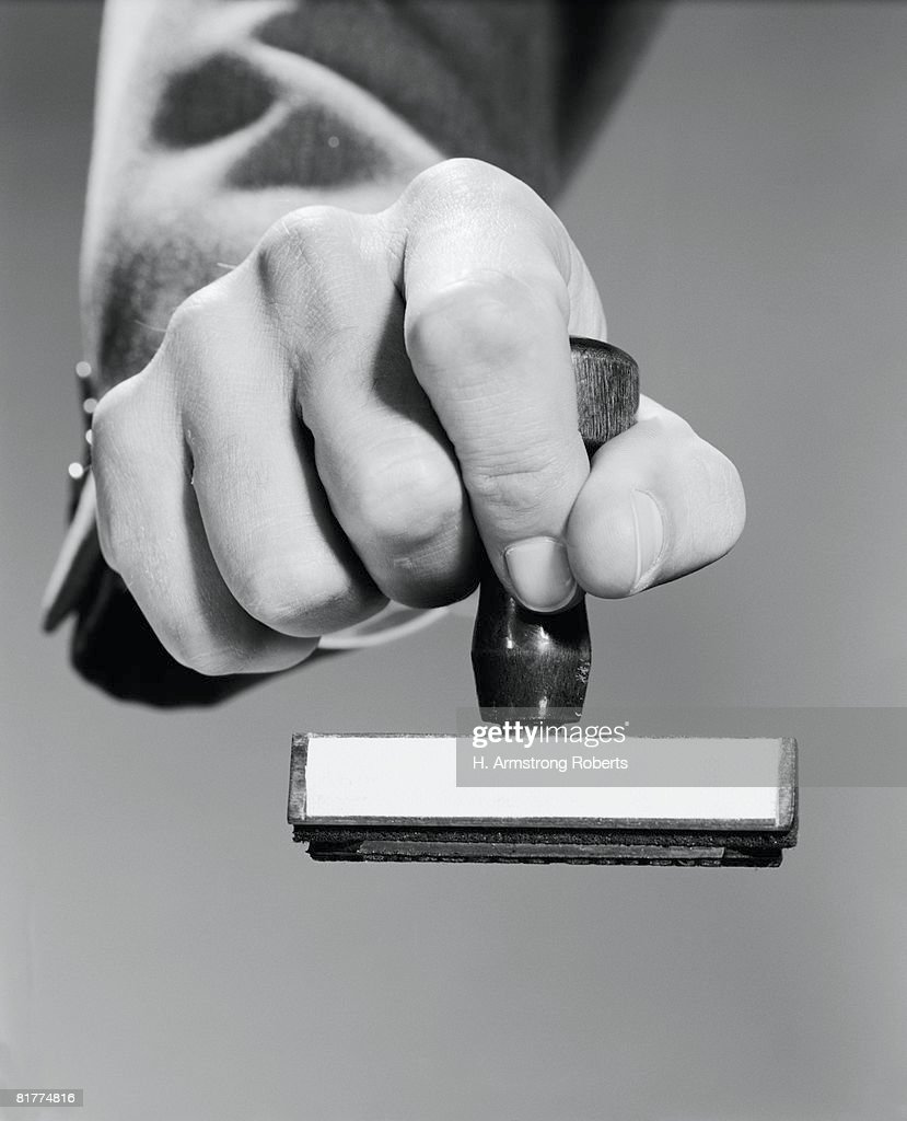 Man's hand holding rubber stamp, poised about to stamp.