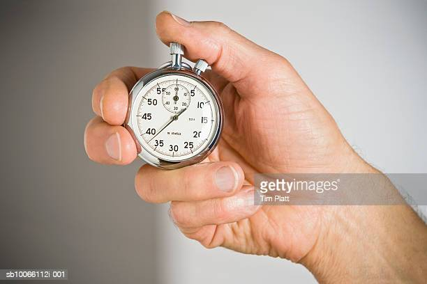 Man's hand holding stopwatch, close-up