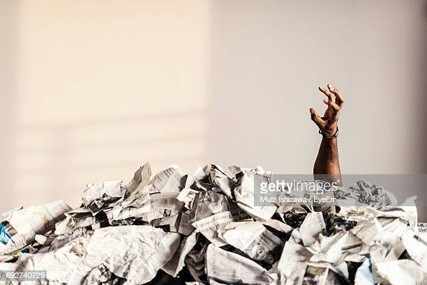 Mans Hand In Stack Of Magazines