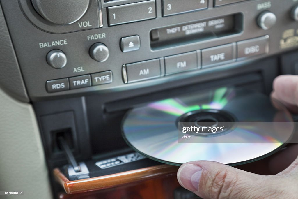 man's hand inserting CD in car player