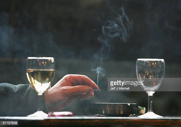 A man's hand is seen holding a lit cigarette as he smokes in a pub March 20 in Glasgow Scotland Smoking in public places in Scotland will be banned...