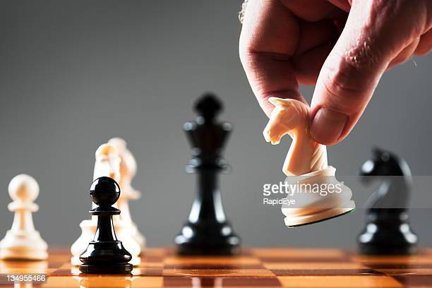 Man's hand moves white knight into position on chessboard