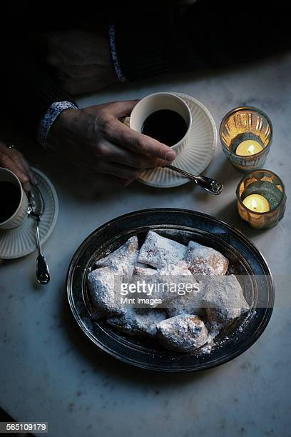 A mans hand on a cup of coffee. A tray of baked pastries.
