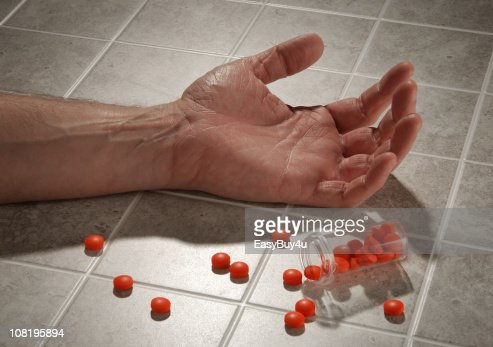 Man's Hand on Floor with Bottle of Pills Spilled