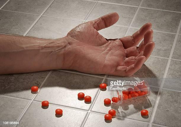 Mann-Hand auf Etage mit Flasche Pillen Spilled