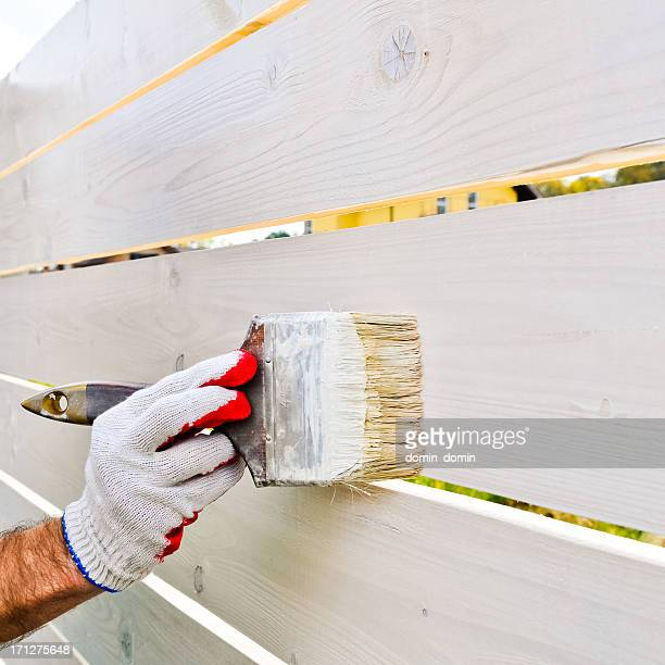 Man's hand painting wooden fence with brush on white colour