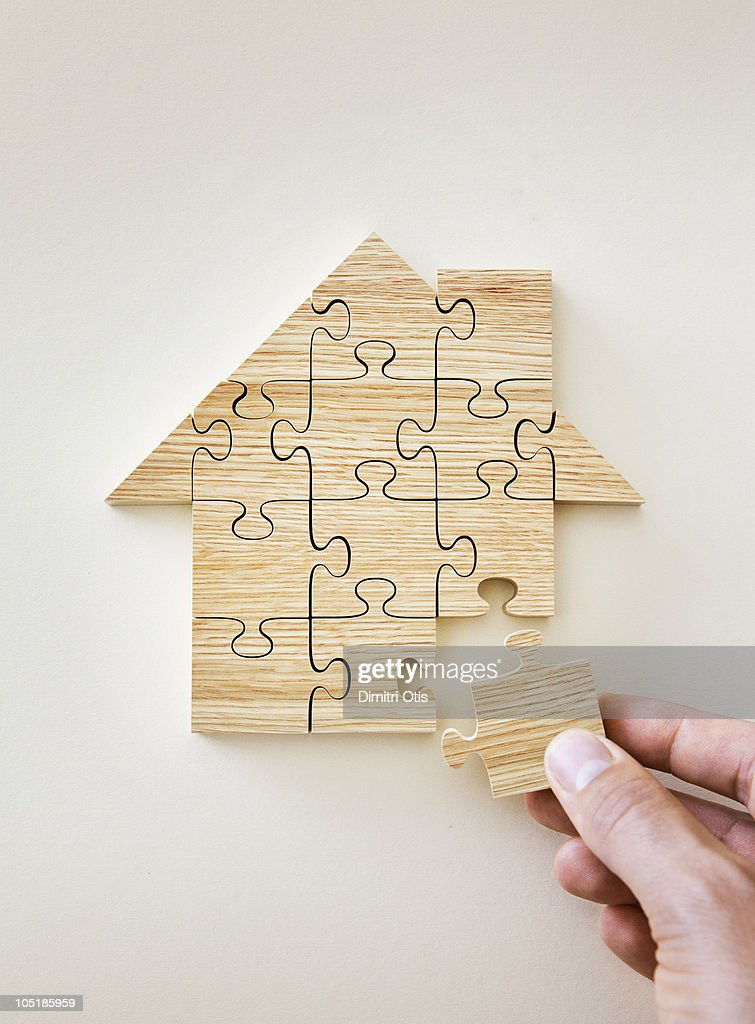 Man's hand placing wooden puzzle piece : Stock Photo