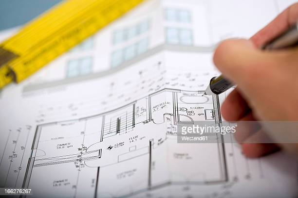 Man's hand pointing at blueprint with pen