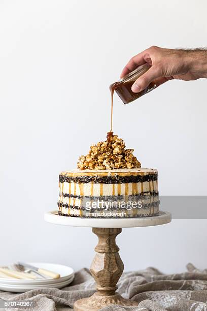 Man's hand pouring caramel on a Chocolate sponge and buttercream cake