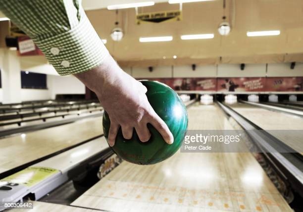 Mans hand ready to bowl green bowling ball
