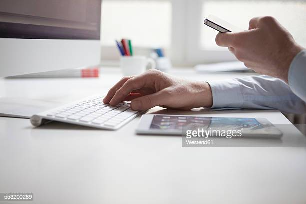 Mans hand typing on keyboard of computer while using smartphone