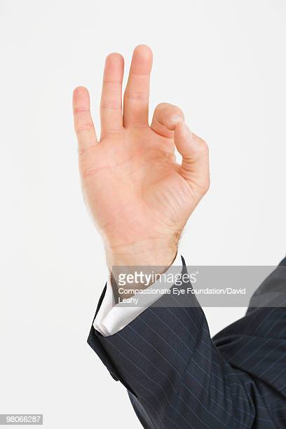 Man's hand with index finger and thumb touching