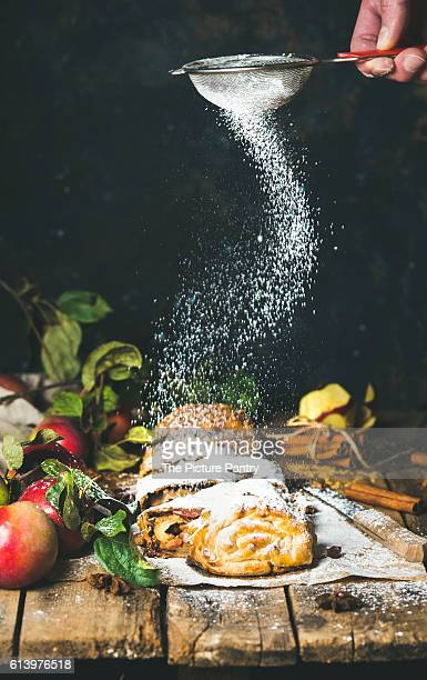 Man's hand with sieve sprinkling sugar powder on apple strudel cake with cinnamon and fresh apples
