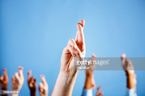 Man's hand with superstitiously crossed fingers, more in blue background
