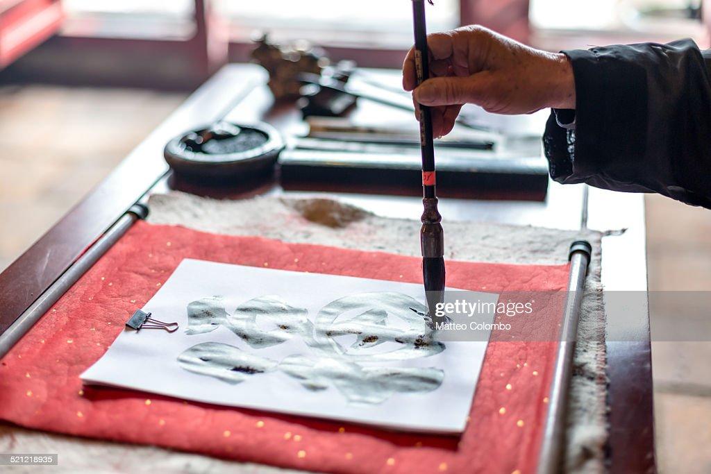 Man's hand writing ancient characters, Vietnam