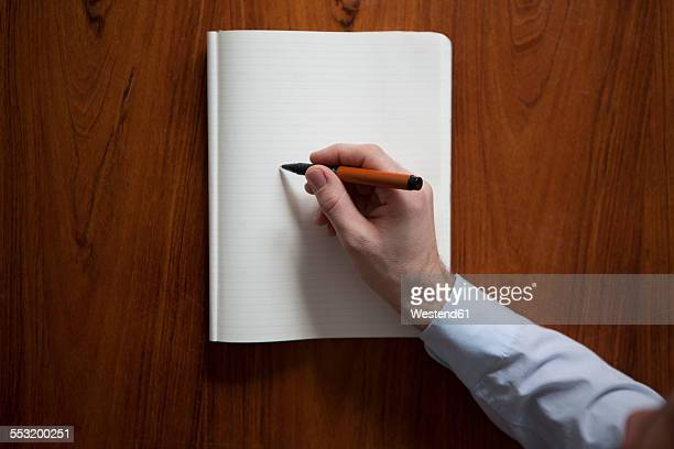 Mans hand writing with ballpen in notebook