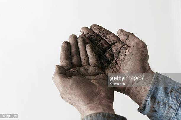 Man's hands covered with dirt
