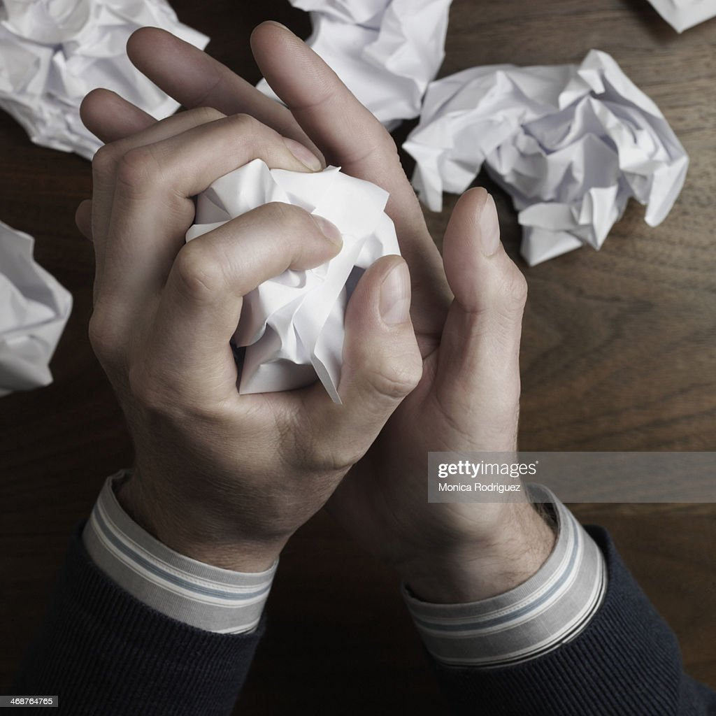 Man's hands crumble writing paper