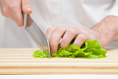 Man's hands cutting green salad leaves with big knife on wooden board. Closeup. Front view.