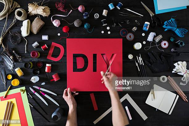 Mans hands cutting out the word DIY of red cardboard