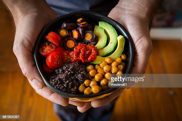 Mans hands holding Buddha bowl of amaranth, avocado, Purple Haze, roasted chickpeas, tomatoes, ajvar