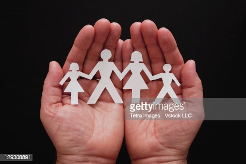 Man's hands holding cut-out representing family