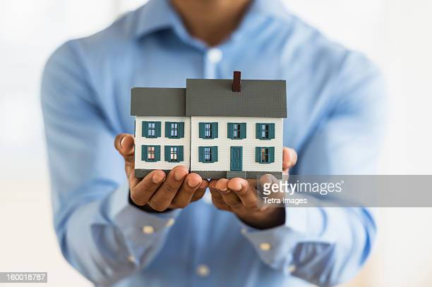 Man's hands holding model home
