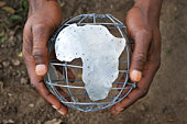 Man's hands holding wire globe showing Africa