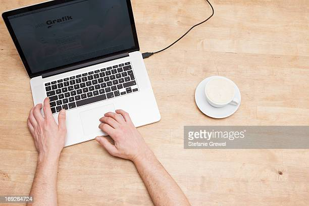 Mans hands, laptop and coffee cup