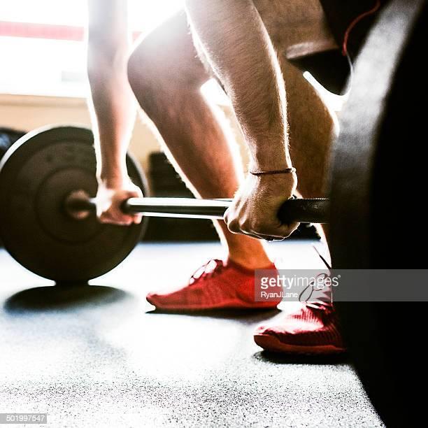 Mans mains sur la barre de poids et haltères