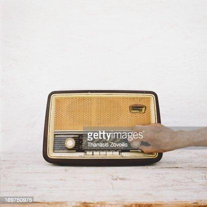 Man's hands on old radio