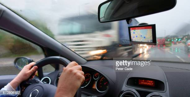Mans hands on steering wheel of car in motion on bust road