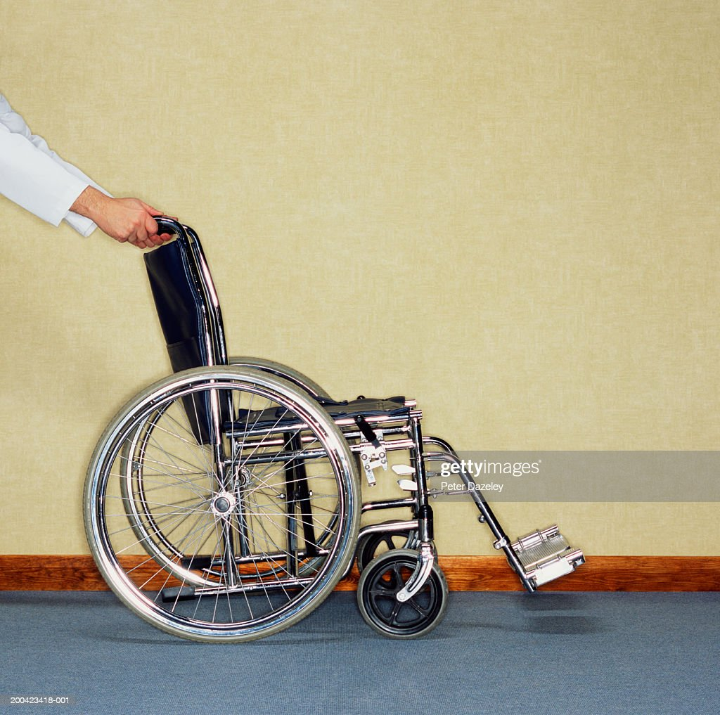 Mans Hands Pushing Empty Wheelchair Side View Stock Photo