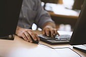 """Business man""""s hands typing away on computer keyboard."""