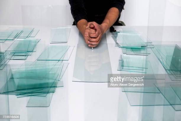 Mans hands using glass cutter on glass pane at workbench