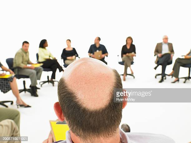 Man's head facing group sitting in circle