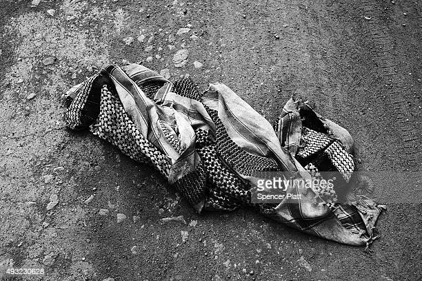 A mans keffiyeh scarf lays next to other items discarded by migrants arriving by boat from Turkey along a Lesbos beach where thousands of objects can...