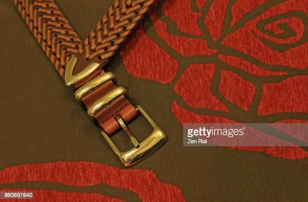 Man's leather belt against a cushion