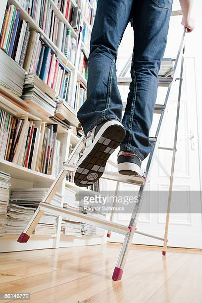 A man's legs climbing up a ladder that's about to tip over