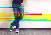 Glitched style photo of young fashion man's legs in jeans and sneakers on wooden floor