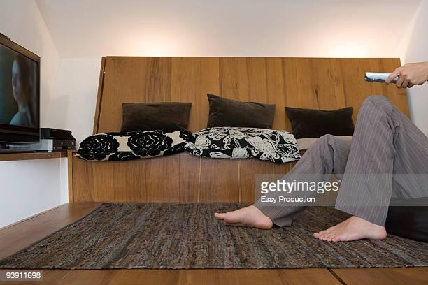 man's legs in front of TV